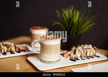 Zwei Tassen heißen Latte mit caramel Kruste gebacken und Brötchen mit Banane und Erdbeere auf dem hölzernen Tisch in Coffe-Shop. Kaffee Konzept. Stockfoto