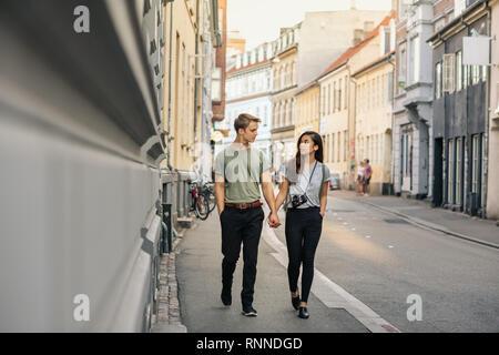 Junges Paar Hände halten und zusammen gesprochen, während auf einem Bürgersteig in der Stadt - Stockfoto