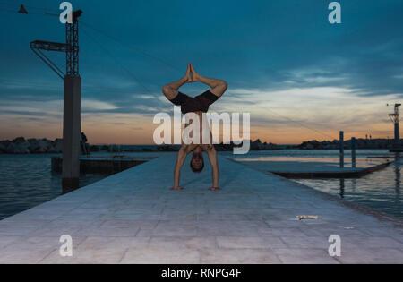 Junge shirtless Sportler tun Handstand auf Pier in der Nähe von Wasser in Abend mit tollen Himmel - Stockfoto