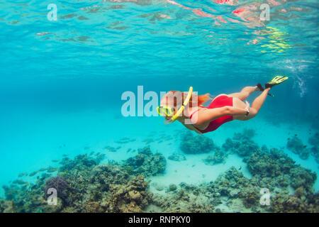 Junge Mädchen in gerne schnorcheln Maske Springen und Tauchen Unterwasser tropische Fische im Korallenriff Meer Pool zu sehen. Reisetätigkeit, Wassersport Abenteuer - Stockfoto