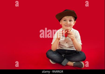 Für Urlaub, Liebhaber Tag und Muttertag, Baby Junge sitzt auf einem roten Hintergrund mit einem roten Herz in seinen Händen. Das Konzept ist auf Geschenke und Liebe geben - Stockfoto