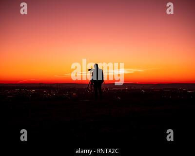 Bild von die Silhouette eines Mannes mit Brille und mit tripot und Kamera auf einem Hügel bei Sonnenuntergang - Stockfoto