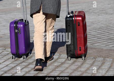 Stilvolle Mann mit zwei Koffer auf Rädern zu Fuß auf der Straße. Männliche Beine und Gepäck auf der gepflasterten Straße, zurück. Konzept für Reise, Eilt - Stockfoto