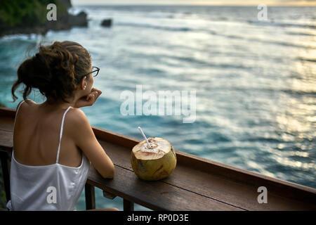 Frau Gläser suchen bei Sonnenuntergang Meer im Café im Freien