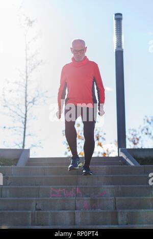 Älterer Mann laufen unten Sonnenlicht Wirkung im Park - Stockfoto