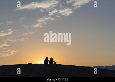 Ein paar sitzt auf einer Düne bei Sonnenuntergang Silhouette gegen die Sonne, Mesquite flachen Sand Dünen, Death Valley National Park, California, United States - Stockfoto