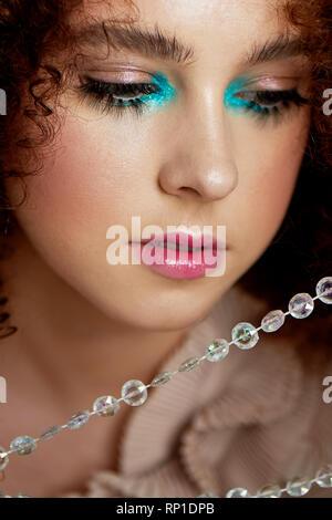 Ein Mädchen mit üppigen lockigem rotem Haar. Eng Puppe falsche Wimpern fotografiert. Doll Make-up. - Stockfoto