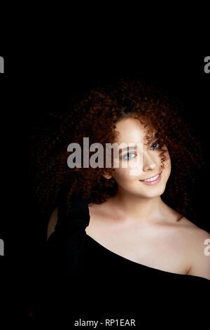 Ein Mädchen mit üppigen lockigem rotem Haar. Schultern öffnen. Korrigiert die Haare und lächelt - Stockfoto