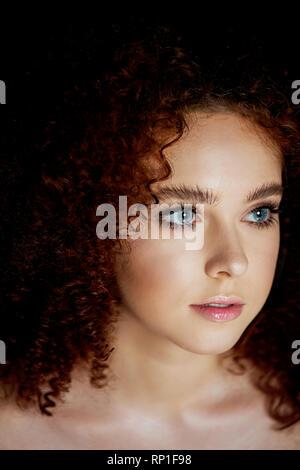 Ein Mädchen mit üppigen lockigem rotem Haar. zarten Make-up mit falschen Wimpern in doll Stil. - Stockfoto