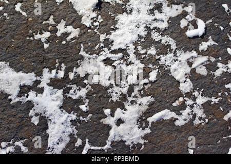 Ansicht von oben Makro Zusammenfassung Hintergrund einer Asphaltstraße bestäubt mit Schnee Muster - Stockfoto