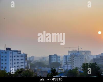 Sonne in Kondapur und HITEC City, Hyderabad, Telangana, Indien. Die Landschaft ist unter am frühen Morgen Nebel und Smog bedeckt, Ende Januar. - Stockfoto