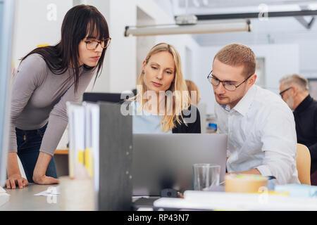 Mannschaft der jungen Mitarbeiter an einem Notebook gesammelt und Suchen am Bildschirm während der Arbeit an einem Projekt. Niedrigen winkel Vorderseite Porträt im Büro inter - Stockfoto