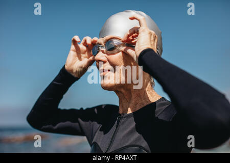 Nahaufnahme von einer älteren Frau in Badekleidung stehen in der Nähe des Meeres. Weibliche Schwimmer stehen am Strand tragen Ihre Badekappe und Schutzbrille. - Stockfoto
