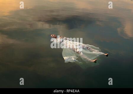 Schwimmende tote Braut im Sonnenuntergang farbigen Wasser - Stockfoto