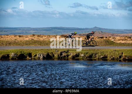 Zwei Radfahrer Fahrt entlang einer Straße vorbei an einem Teich auf Dartmoor in Devon, Vereinigtes Königreich. - Stockfoto