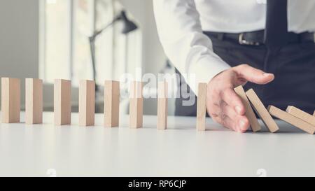 Business Krisenmanagement Konzept - wirtschaftsmediator stoppen fallende Dominosteine mit seiner Hand. - Stockfoto