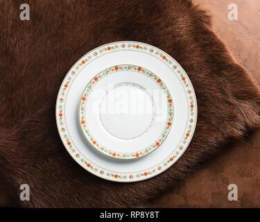 Weiße Platten mit Ornament leer auf einem Braunen strukturierten Hintergrund. Kopieren Raum Platz für Design. Flachbild Layout. - Stockfoto
