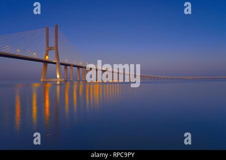 Elegante steel Bridge bei Nacht vorbei an Kilometer über große ruhige Fluss Wasser - Stockfoto