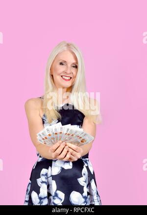 Glückliche, attraktive blonde Frau und ein Haufen von zehn Pfund stellt in einem Ventilator Form gehalten und gegen einen rosa Hintergrund genommen - Stockfoto