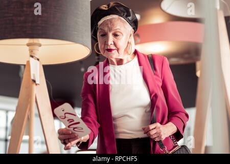 Betörend elegante älteren Dame Zu Verkaufen - Schild in der Hand auf der Suche - Stockfoto
