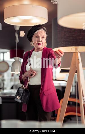 Eleganten französischen Stil altern freundliche Dame in Beleuchtung showroom - Stockfoto
