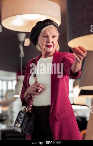 Das Porträt von anspruchsvollen Frau Kontrolle Lampe Qualität in Store - Stockfoto