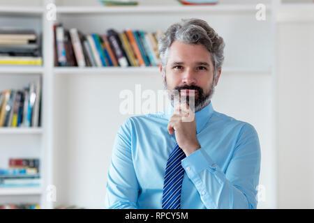 Ernsthafte Geschäftsmann mit grauem Haar und Krawatte im Büro - Stockfoto