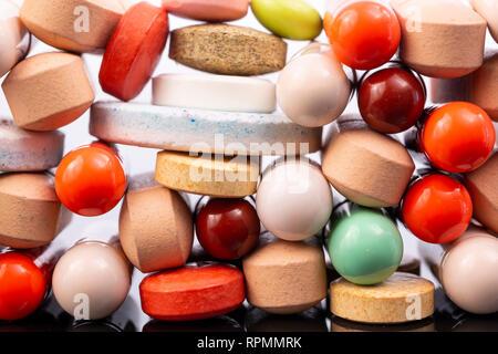 Verschiedene bunte Pillen und Kapseln gestapelt. Globale pharmazeutische Industrie für Milliarden Dollar pro Jahr. Medikamente für den Einsatz als medicatio - Stockfoto