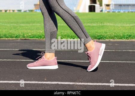 Mädchen Beine in rosa Sport Schuhe auf einem Laufband mit Stadion steht. Sport und gesunde Konzept. - Stockfoto