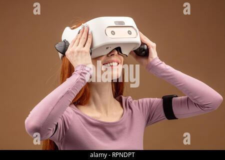 Casual Ingwer - behaarte Frau in Lila pullower tragen VR-Headset und Suchen in 3-D-Simulation Spiel beteiligt, Gestik, die Hände, als wenn er mit der Interaktion - Stockfoto