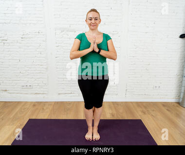 Portrait der junge lächelnde attraktive Yogi Lehrerin Frau Yoga in namaste Pose in coolen Urban Style Studio in Workout Fitness beten - Stockfoto