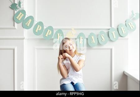 Süße kleine blonde Mädchen sitzt in einem hellen Raum in der Nähe der Fenster auf dem Hintergrund der Streamer mit der Aufschrift Frohe Ostern - Stockfoto