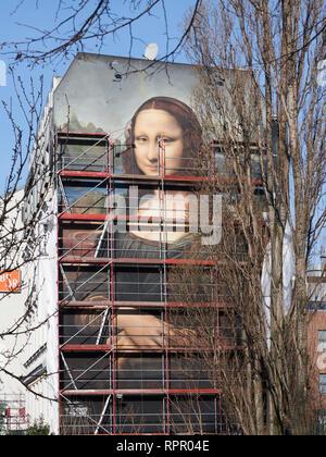 Berlin, Deutschland. 23 Feb, 2019. Ein Gerüst wird abgebaut und die übergroßen Mona Lisa blickt auf die Straße an der East Side Gallery. Der Berliner Künstler kollektive Dixons sterben, zusammen mit den Künstlern Tank, Weisse Seite und FIX 77, hat eine Replik von Da Vincis Mona Lisa in einer Größe von 16,30 und 10,60 Meter auf der Firewall von einem Hotel in der Mühlenstraße lackiert gegenüber der East Side Gallery. Quelle: Annette Riedl/dpa/Alamy leben Nachrichten - Stockfoto