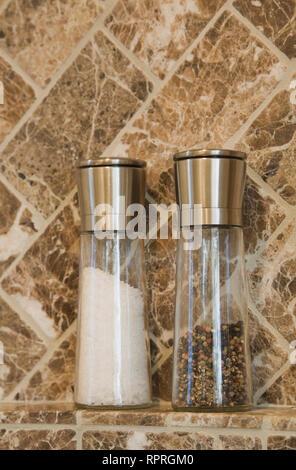 Close-up aus Edelstahl und Glas Salz und Pfeffer Shaker auf Arbeitsplatte gegen eine Marmor Wand Hintergrund in einem luxuriösen Land Küche. - Stockfoto
