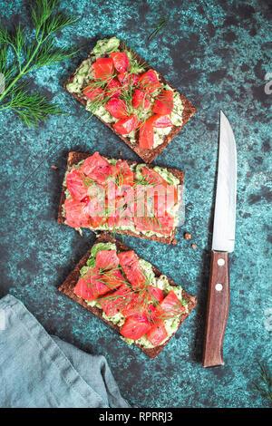 Drei Sandwiches mit Roggenbrot, Avocado, geräucherten Lachs auf blauem Hintergrund. Ansicht von oben, flach. - Stockfoto