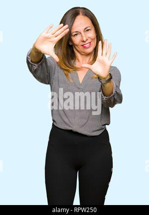 Schönen mittleren Alter business Frau lächelnd tun Rahmen mit Hände Handflächen und Finger, Kamera Perspektive - Stockfoto