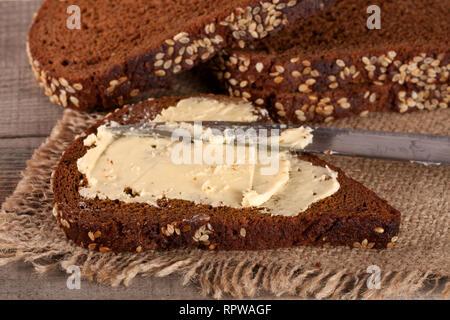 Scheibe Schwarzbrot mit Sesam und Butter auf einem alten Holz- Hintergrund - Stockfoto