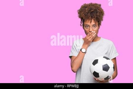 Junge afrikanische amerikanische Frau mit Fußball-Fußball-Kugel über isolierte Hintergrund decken den Mund mit der Hand schockiert mit Schande für den Fehler, den Ausdruck von - Stockfoto