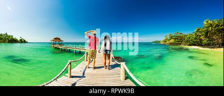 Schöne junge Paar entspannende auf einer exotischen Strand von Seychellen. Verliebtes Paar auf Hochzeitsreise auf exotischen Insel Stockfoto