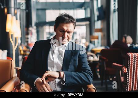 In der Nähe der gut aussehende junge Mann sitzt in einem Café Bar, mit Blick auf seine Hand beobachten, wie er darauf warten, dass jemand kommt und eine geschäftliche Besprechung haben - Stockfoto