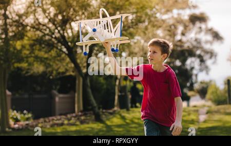 Junge spielt mit einem Spielzeug Flugzeug in den Park an einem Sommertag. Junge läuft mit einem Spielzeug Flugzeug im Freien. - Stockfoto