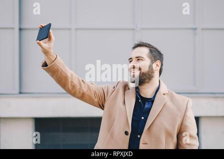 Close-up Portrait von attraktiven und modernen jungen Mann eine selfie mit seinem Handy, das Tragen modischer Kleidung und posieren für Social Media fo - Stockfoto