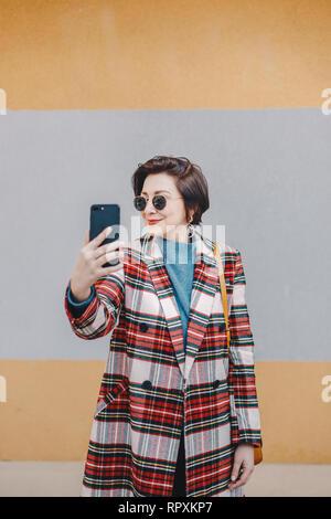Porträt der moderne junge Frau eine selfie mit Handy, tragen schicke Kleidung und posieren für online-Freunde vor bunten backgro - Stockfoto