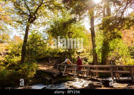 Menschen, die über eine Holzbrücke über den Fluss - Stockfoto