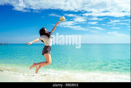 Glückliche junge Frau im lässigen Stil Mode und Strohhut am Sandstrand springen. Entspannung und Urlaub im tropischen Paradies Strand mit blauem Himmel genießen und - Stockfoto