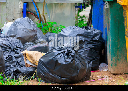 Schwarzer haufen Müll am Straßenrand und Regen fällt auf die Tasche in der Stadt mit Kopie Raum Text hinzufügen