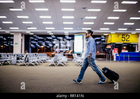 Asiatischer mann Reisende mit Koffern zu Fuß und Transport auf einem Flughafen - Stockfoto