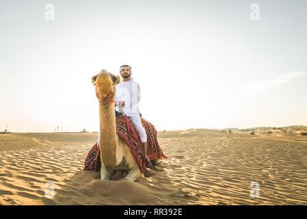 Stattlich im Nahen und Mittleren Osten Mann mit kandura und gatra reiten auf einem Kamel in der Wüste - Stockfoto