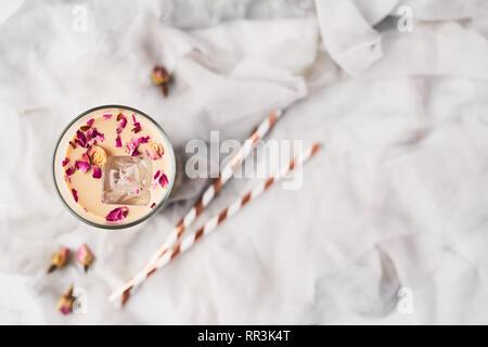Eiskaffee mit Rose und Kardamom in ein hohes Glas mit getrockneten Rosen und Strohhalme auf weißer und grauer Seide Hintergrund umgeben. Ansicht von oben mit der Kopie Raum fo - Stockfoto