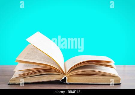 Buch mit offenen Seiten auf einer hölzernen Oberfläche auf einem blauen Hintergrund - Stockfoto